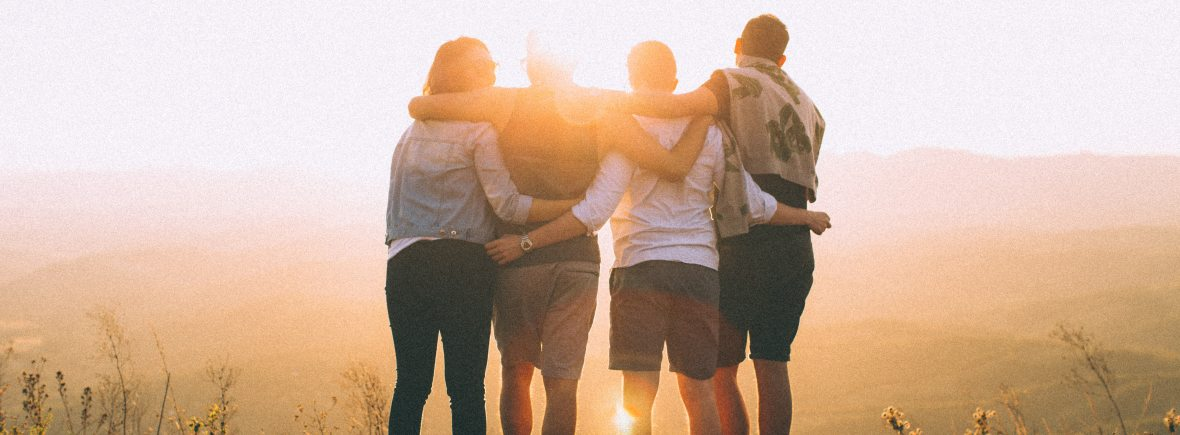 friends hugging watching sunrise landscape