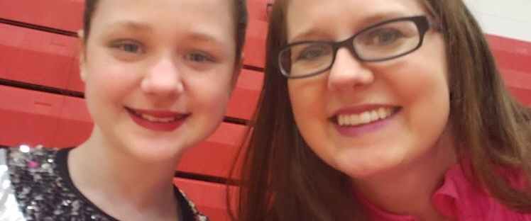 A young woman in a dance uniform smiles with her mother in a gym.