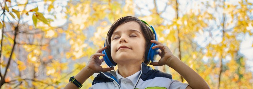 Young boy closing his eyes listening to headphones in the park